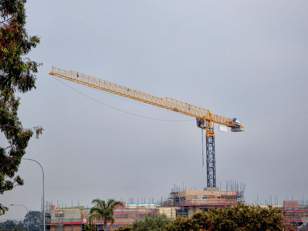 high crane balance1: high crane at building construction site with darkening hazy winter sky