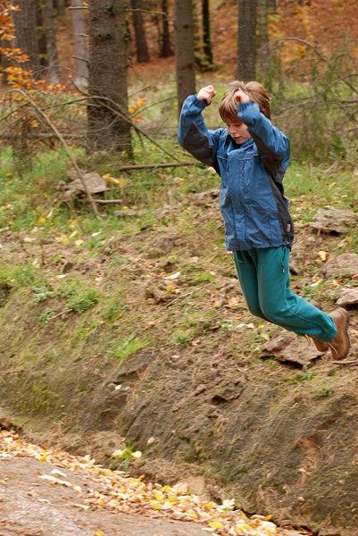 Boy activity: Kid jumps in autumn forest
