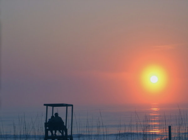 Lovers Dawn: Sorry, another sunrise, but I couldn't resist! A close couple enjoying the break of a new day on a lifeguard seat at the beach. Adjusted Gamma