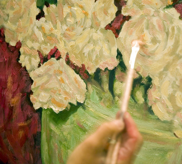 Painting in oils: An artist busy with a still life in oil paints.NB: Credit to read