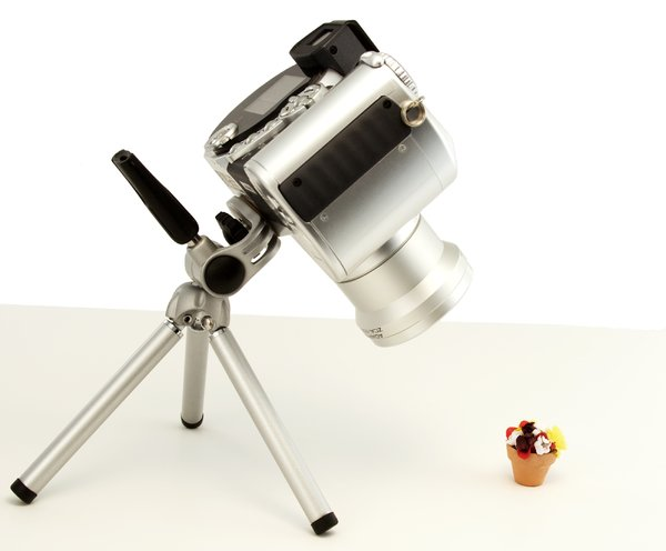 Macro Photography: A camera poised to photograph a one inch clay pot of silk flowers.