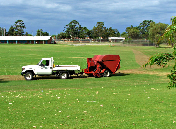 preparing the greens: workmen and machinery preparing and maintaining green sporting field