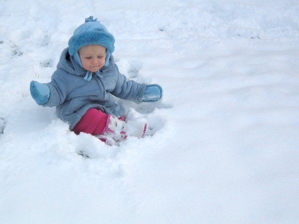First Snowfall: Young toddler playing in the snow for the first time.