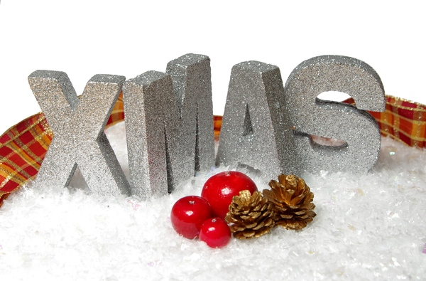 Xmas ribbon and  snow: Silver letters spelling XMAS in decoration snow with ribbon, red apple, red berries and golden cones