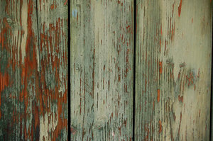 Wood door texture: Green painted wooden door with cracked painting.