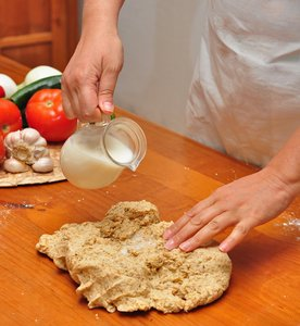 Pouring milk on pizza dough: Woman pouring milk on whole-wheat pizza dough over a wooden table