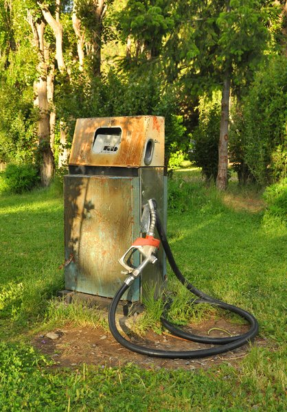 Abandoned gas pump: Abandoned gas pump, with grass and trees in the background