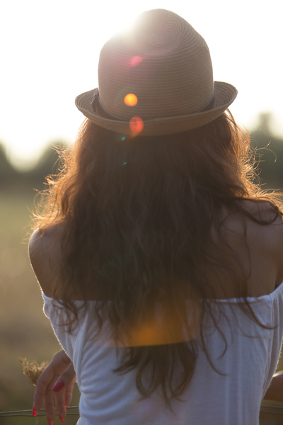 Country Girl: Young woman looking to the horizon with the sun making a lens flare.