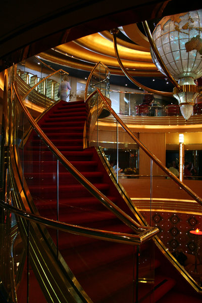 Grand Golden Staircase: Curved, red carpeted, gold handrail staircase.