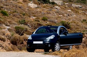 Open car on mountain: A small open car (cabriolet - convertible) on a dusty mountain road.