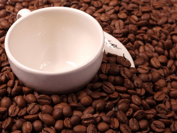 Coffee beans and an espresso c: A coffee cup and saucer covered with coffee beans