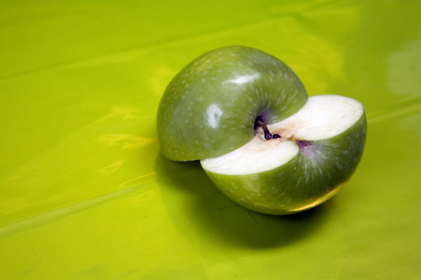 two halfs: two hlfs of green apple on the green vivid background