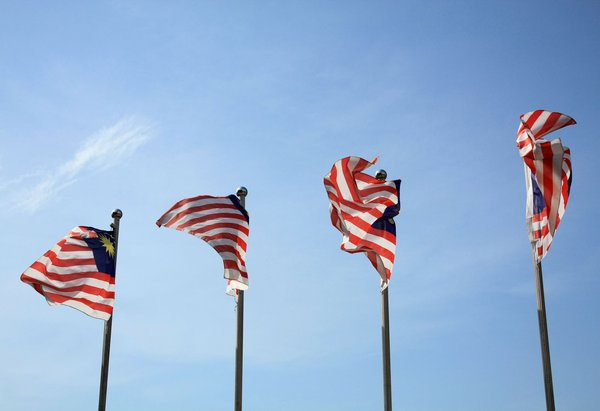 Stripes Of Glory: Flags flapping in the wind against a sunny clear blue sky