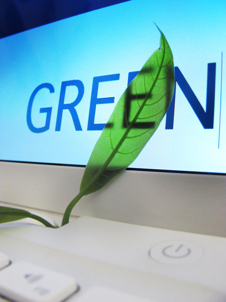 green computing: laptop screen detail with green leaf & text