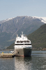 Ship: A large cruiser moored at a small jetty in a fjord in Norway.