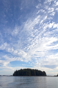 Island below the sky: Tiny island and big sky off the coast of western Vancouver Island, Canada.