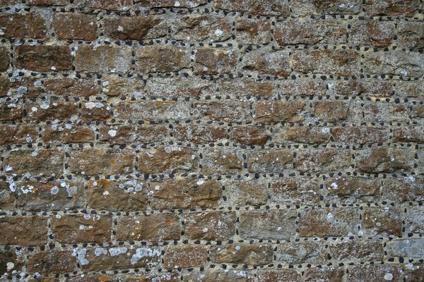 Old church wall: Stone wall of an old church in Surrey, England, with the mortar studded with tiny black stones.
