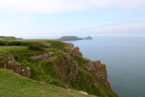 Sea cliffs: Cliffs terminating at the Worm's Head, Gower, Wales, UK