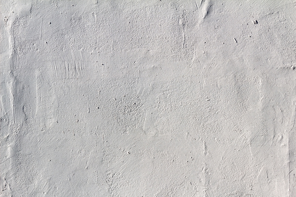 Grunge texture: A rough plaster wall painted white.
