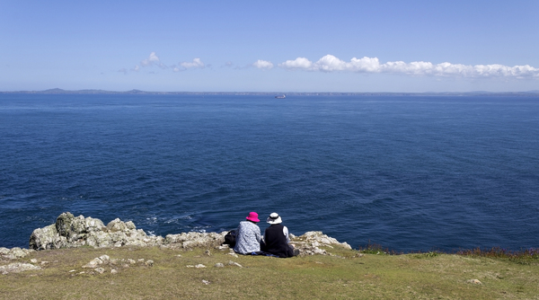 Admiring the view: An elderly couple enjoying a view of coastline of Pembrokeshire, Wales.