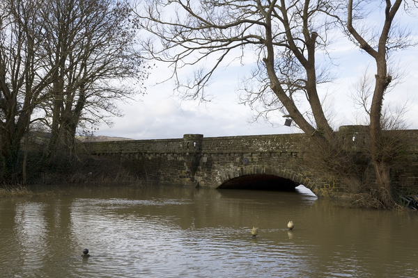 Bridge in flood water: An old bridge at Amberley, West Sussex, England, almost engulfed by a flooded river.