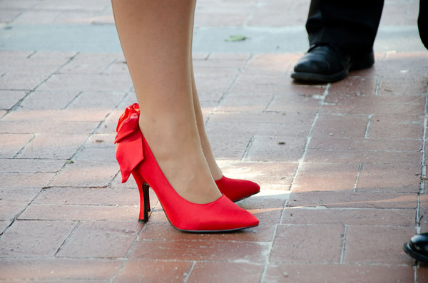 Red Pumps: Red high heel shoes on red tiles with mens shoes in the background