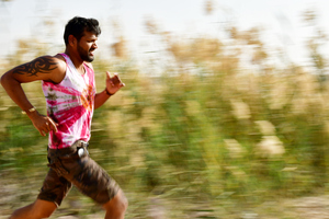 Young runner is jogging: Young man Jogging in nature for fitness and healthy weight loss. Nature greenery is around and the young adult is running wearing sport clothes and shorts.