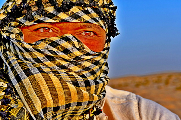 Arab man in the desert: Portrait of Arab man in the desert of Saudi Arabia, Skin dark and red from the heat and sand all around him .  Photo image for wall art, artwork or local art . Burka is covering his head except his eyes .