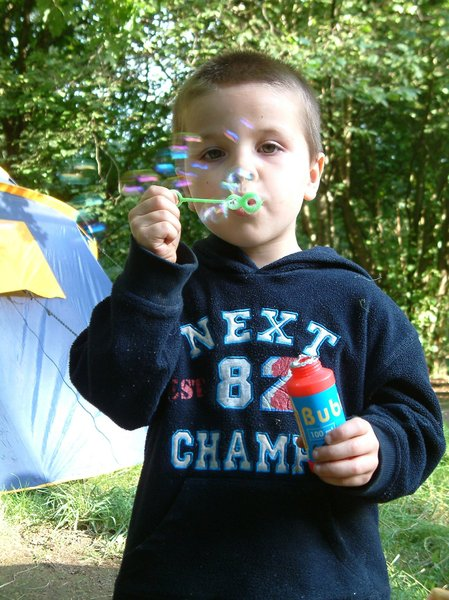 Blowing bubbles: Small boy blowing bubbles at camp.
