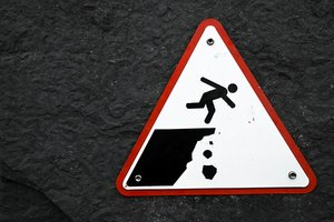 Cliff Drop Warning Sign: Cliff drop warning sign on a stone wall.