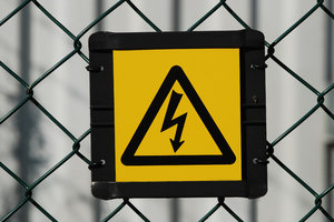 Chocking Sign: High voltage warning at larger electrical station.