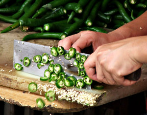 chillie chop: food handler chopping up green chillies