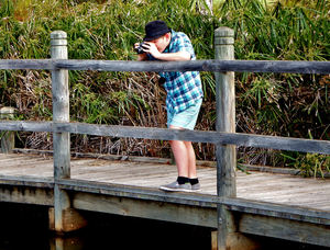 young enthusiast1: enthusiastic preteen photographer trying out a camera on lakeside over-the-water wooden walkway