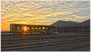 Railway Carriage: A burnt-out shell of a railway carriage in a goods yard at sunset