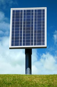 Solar Panel: Solar panel against a blue sky and green grass
