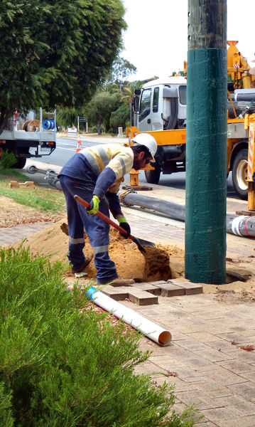 power pole replacement18: deteriorating old power pole being replaced with new pole  --  workman filling in the hole & stabilising new power pole