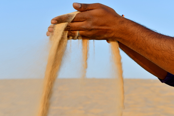 Sand in the hand of an Indian: Sand of the desert picked up by one man from India and is poured back from his hand , its red sand of the Saudi Arabian desert which-is the travel destination for this men from India, visiting and traveling to the desert to enjoy the desert beauty the des