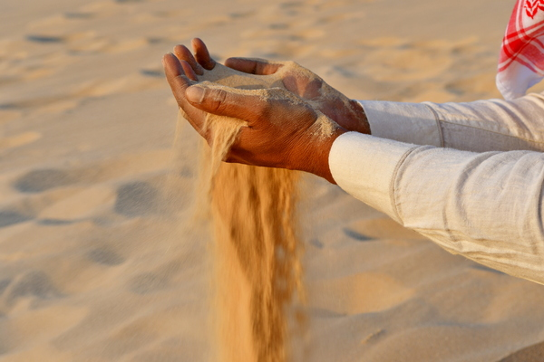 Pouring the sand: Sand of the desert picked up by one man from India and is poured back from his hand , its red sand of the Saudi Arabian desert which-is the travel destination for this men from India, visiting and traveling to the desert to enjoy the desert beauty the des