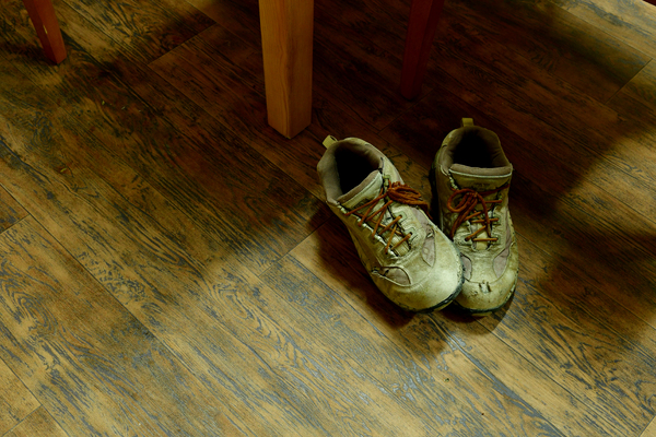 Used Old safety shoes: Old safety shoes, sitting under a table in the house, Shoes on the floor,  dirty Old shoes for men, the wooden floor and the wall are wooden and brown colour with wood grain is the texture of the floor and wall.