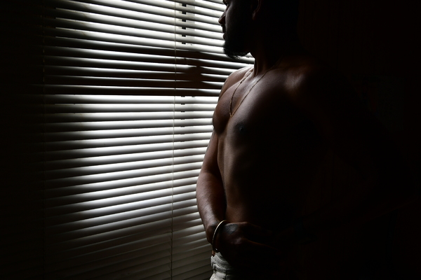 Dark Silhouette of a man: Man standing near striped window and he is darkness and his body is almost a silhouette. Dark Background against striped light and shadows.
