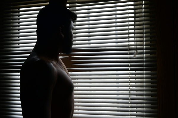 young man in the darkness: Fitness model of a young man is standing and facing out the window through the striped patterned light and shadow shuttering. The  man is in darkness and his body in dark shadows almost silhouette.