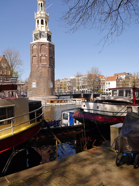 City tower along canal & boats: Photo of one of the old city-towers of Amsterdam, built in 17th century and still in original Dutch architecture. The tower is located along the canal with a lot of houseboats. A city view in sunlight and shadows of the tree branches.