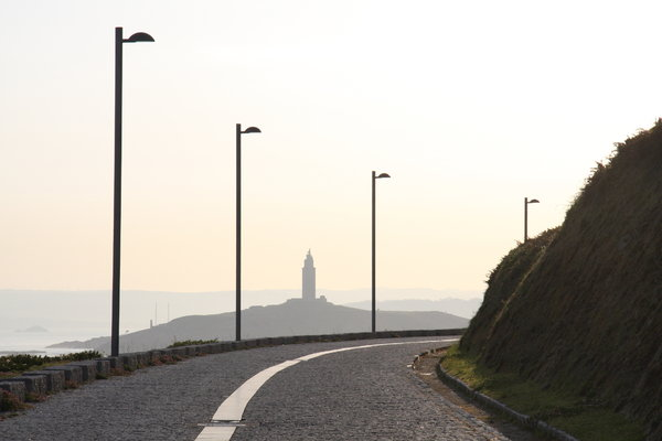 On the road: On the road in A Coruña. The oldest lighthouse working in the world as background.