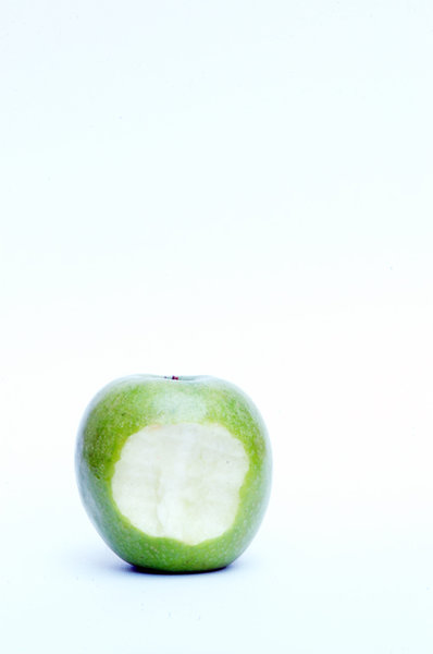 Green apple with bite in middl