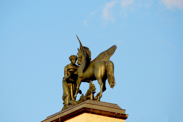 Statue of maid with pegasus: Golden figures from greek mythology, on the roof in Berlin