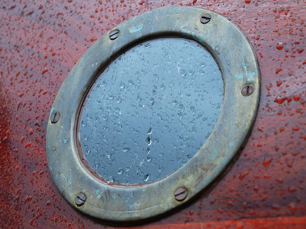 Boat Porthole: Window on an old wooden boat.