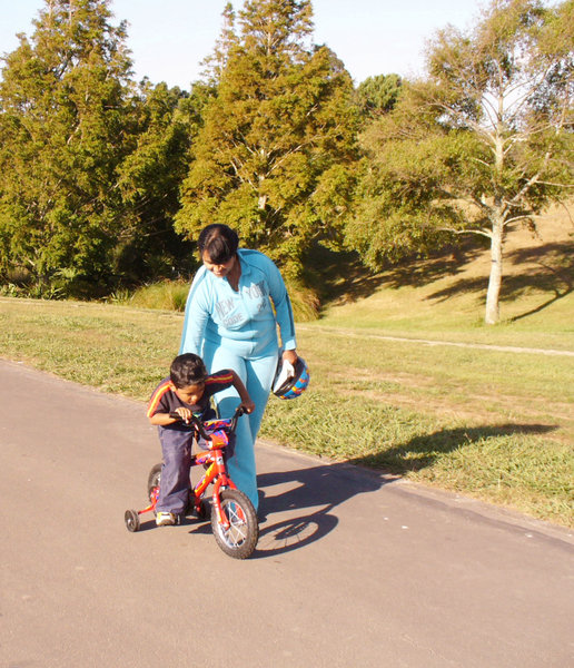 A helping hand 1: Mother gives her son a supporting hand while learning to ride his bicycle