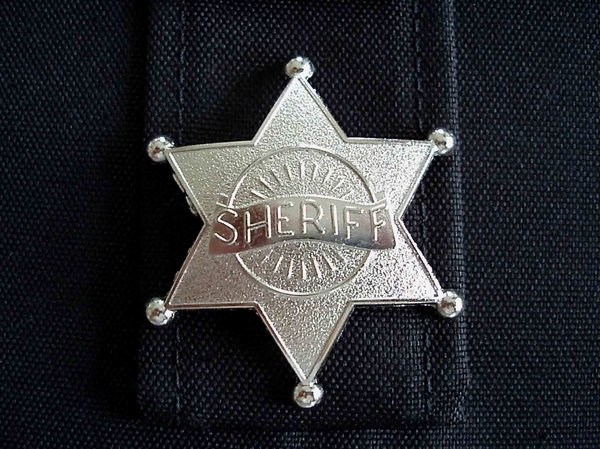 Sheriff: Silver sheriff badge on a black cloth background