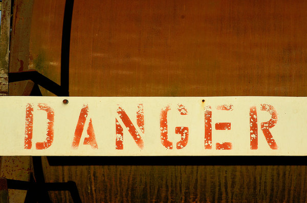 Danger: Faded danger sign on an old rusty machine.