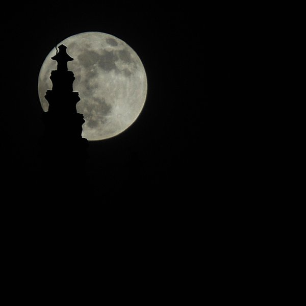 moony in spired: the moon silhouetting a church spire.